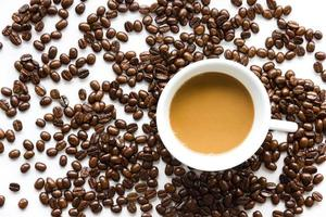 White coffee cup and coffee beans .