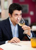 uomo bello che beve un bicchiere di vino