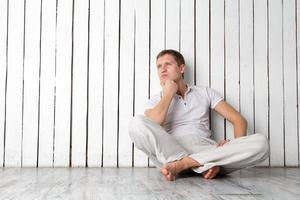 Thinking man sitting near the wall