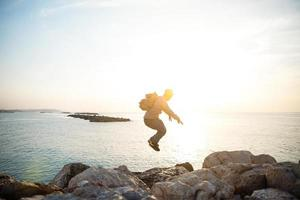 traveler jumping over rocks near the sea