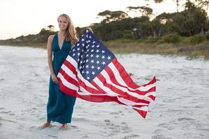 Woman holds American flag while standing on the beach photo
