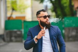 man with a beard smokes electronic cigarette