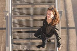 Beautiful smiling young woman on the stairs photo