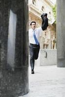 Businessman running on city street