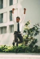 Cheerful Businessman Jumping Celebrating Success photo