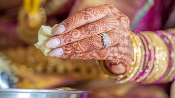 las manos de la novia del sur de India mientras ella come comida india, foto