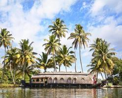 House boat on river in tropics with palm trees