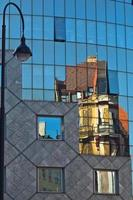 Reflection of old style buildings in glass of Haas House