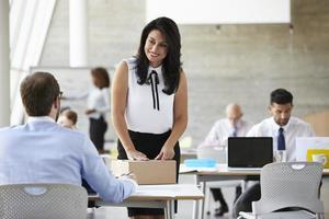 Businesswoman In Office Addressing Package For Shipping photo