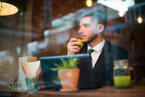 Businessman using laptop computer in coffee shop photo