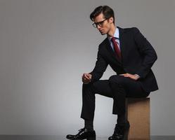 side view of a sitting businessman wearing glasses