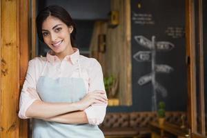 Retrato de sonriente camarera de pie con los brazos cruzados