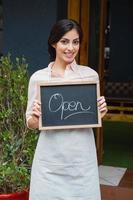 Retrato de camarera con cartel abierto en la entrada