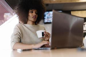 Portrait of attractive afro woman using laptop at the coffee shop