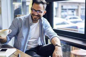Alegre hábil empresario bebiendo café en la cafetería favorita preparándose para una conferencia importante con colegas que disfrutan de un clima soleado y tiempo libre sentados cerca de la ventana esperando la llamada telefónica foto