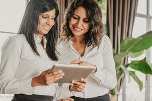 Two smiling female colleagues reading news on tablet in cafe