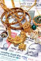 Closeup of gold ornaments on Indian currency photo