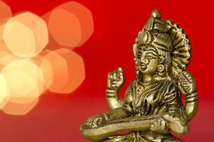 Cerca de una estatua de la deidad hindú sobre fondo rojo.