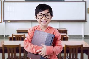 pequeña colegiala con un libro en la clase