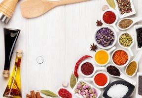 Various spices and condiments on white wooden background photo