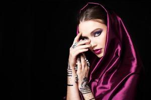 mujer hermosa en estilo oriental con mehendi rezando