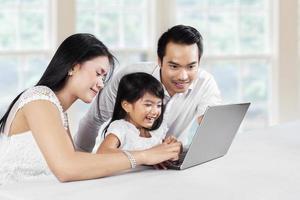 los padres enseñan a su hija a usar la computadora portátil foto
