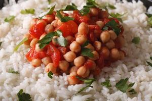 Rice with chickpea curry and herbs macro background