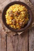 Rice with meat and vegetables on table  vertical top view