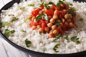 Rice with chickpeas, tomatoes and herbs close-up. Horizontal