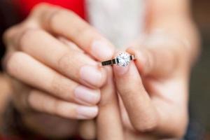 mulher segurando o anel de diamante de casamento / noivado