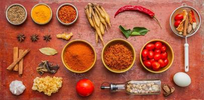 Mixed spices and herbs on red background.