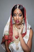 mujer india en vestimentas tradicionales con maquillaje de novia y joyas