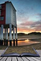 Beautiful landscape sunrise stilt lighthouse on beach conceptual photo