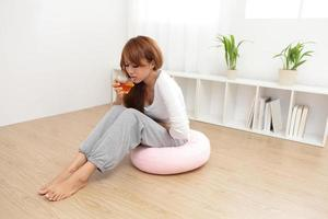 A woman on a pink cushion holding her stomach and drinking