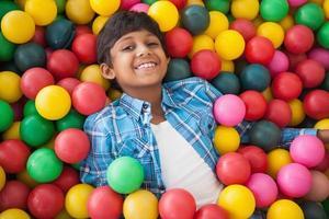 chico lindo sonriendo en la piscina de bolas