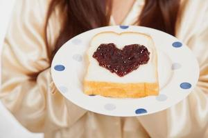 Asian woman  with bread and heart shape berry jam