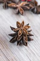 Star anise stacked over wooden background