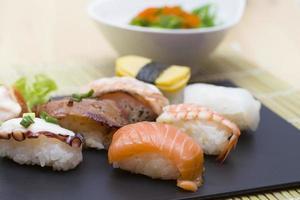 Sushi assortment on black dish, close up photo