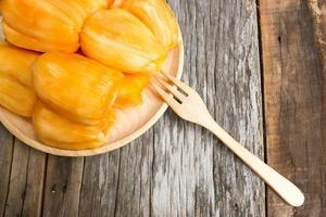 Jack fruit in wooden plate  on old wood background.