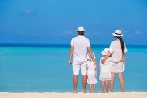 joven familia de cuatro en vacaciones en la playa foto