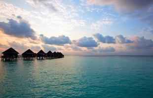 villa sur pilotis dans l'eau au coucher du soleil.