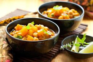 Three black bowls filled with pumpkin curry and side dishes