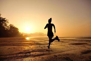 young fitness woman running on sunrise beach