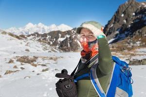 Young woman backpacker tourist standing snow mountains ridge por