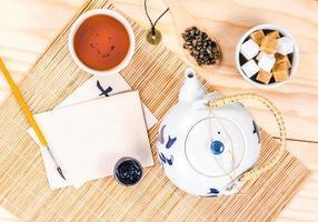 cartão em branco e conjunto asiático de chá na mesa de madeira
