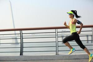 corredor de mujer joven fitness corriendo a orilla del mar foto