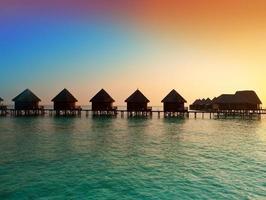 île dans l'océan, villas sur pilotis au coucher du soleil.