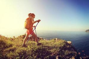 mujer joven de senderismo en el sendero de montaña junto al mar foto