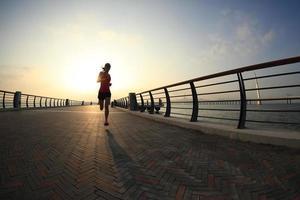 corridore di giovane donna fitness in esecuzione in riva al mare