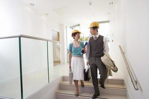 Businessman and woman with briefcases in hard hats on stairs